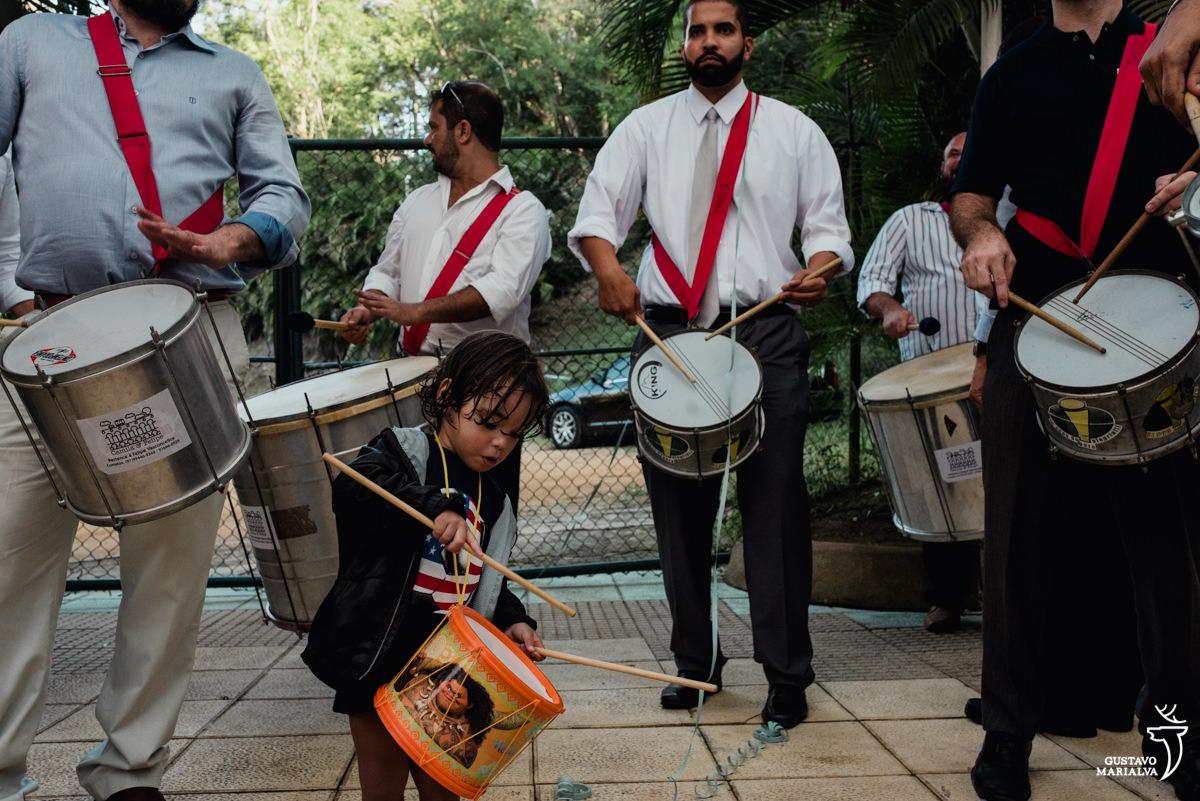 menino toca tambor acompanhado de homens tocando caixa e surdo