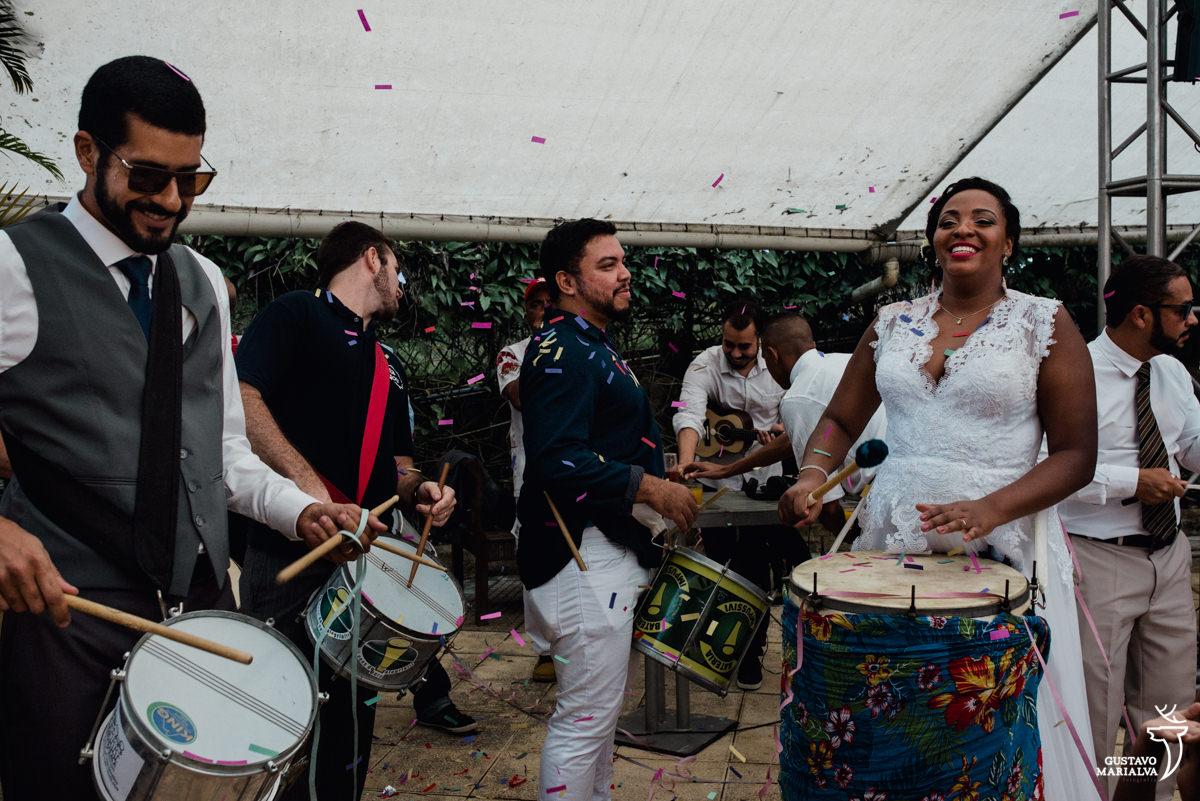 bloco de carnaval toca na festa de casamento com a noiva tocando surdo e o noivo tocando caixa