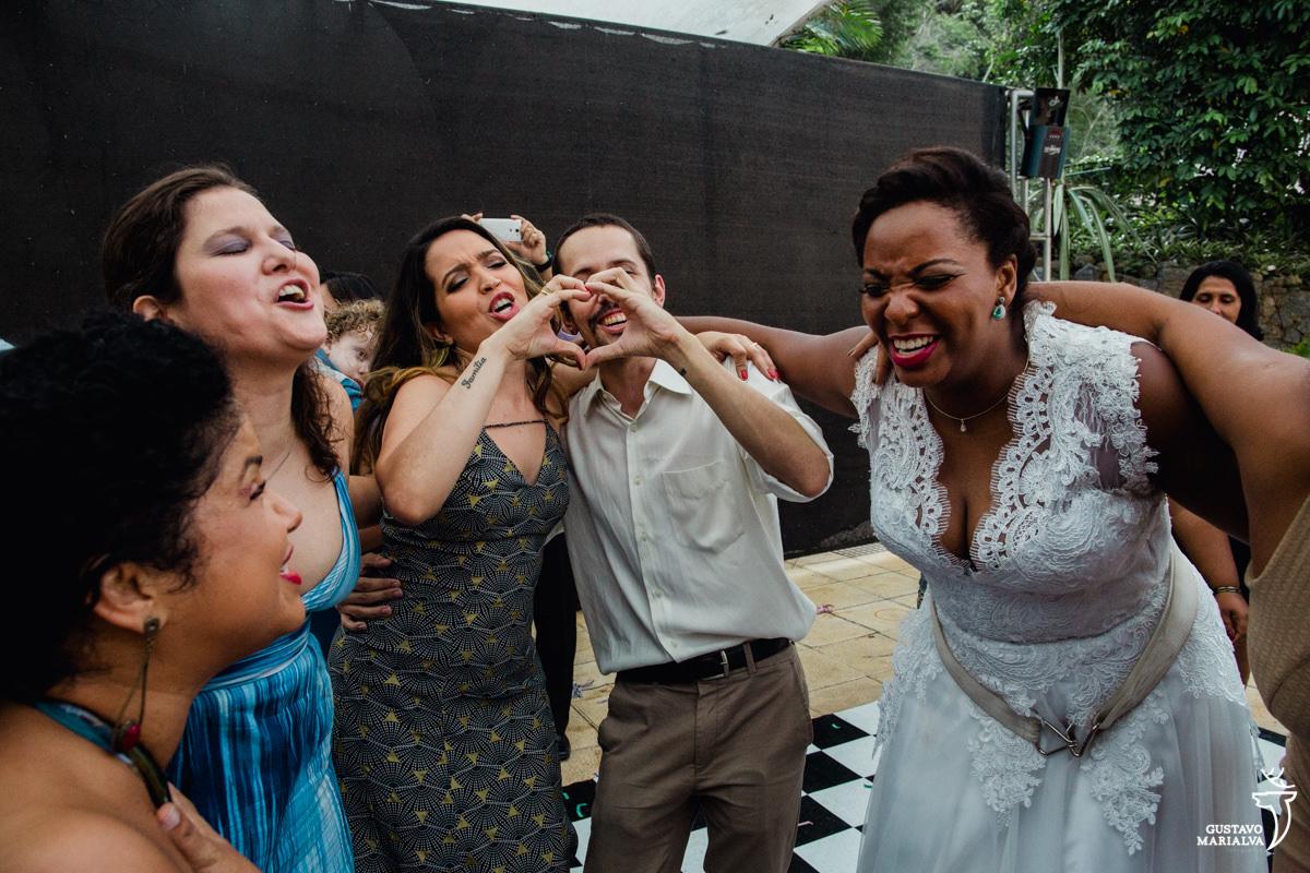 noiva sorri emocionada abraçada aos amigos enquanto convidados fazem coração com a mão