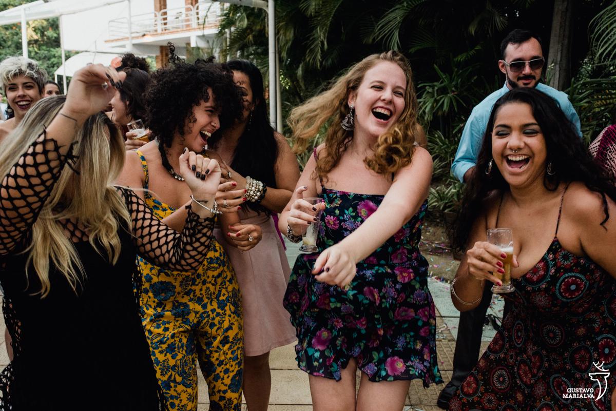 amigas com copo de cerveja nas mãos dançam sorrindo