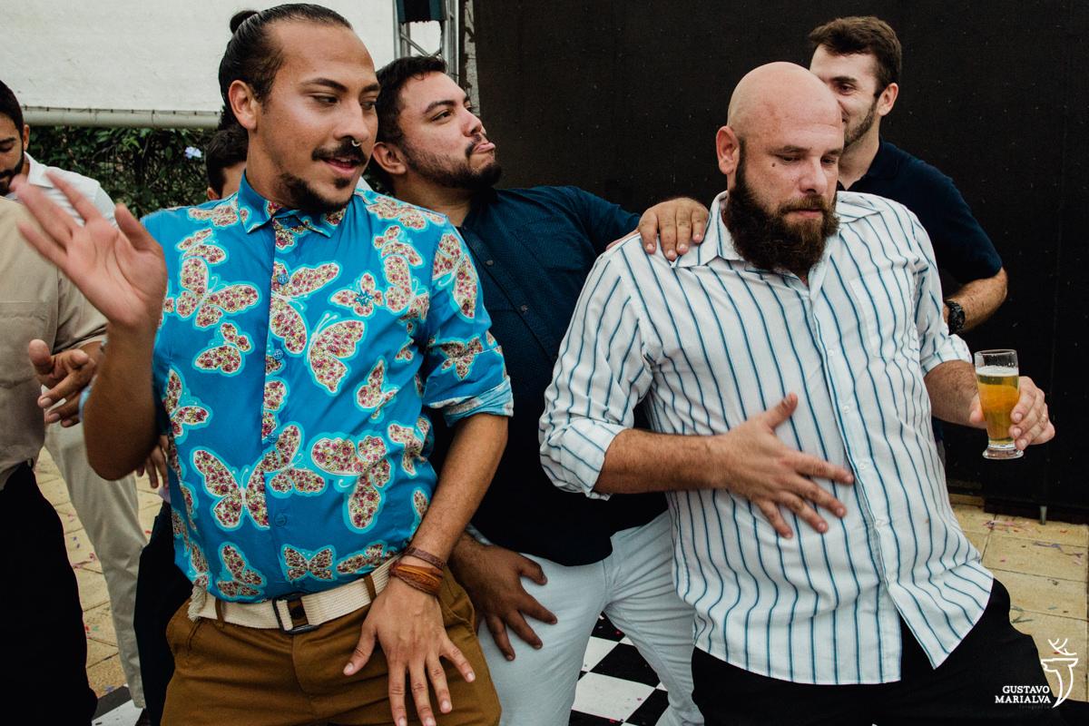 convidados dançam fazendo careta com a mão na barriga