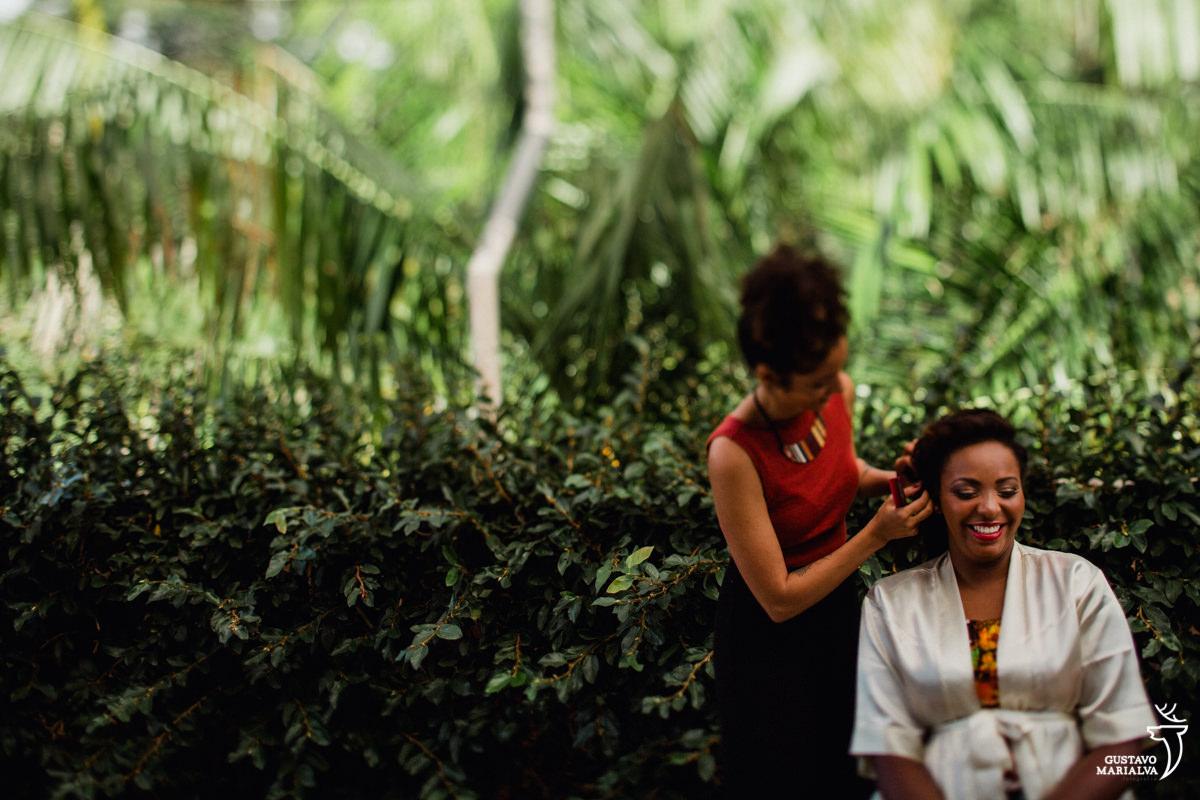 maquiadora ju sales arrumando o cabelo da noiva que sorri durante o making of do casamento no bosque da fazenda