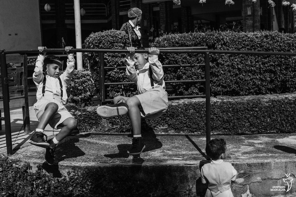 pajens brincam pulando da escada enquanto mulher limpa o chão