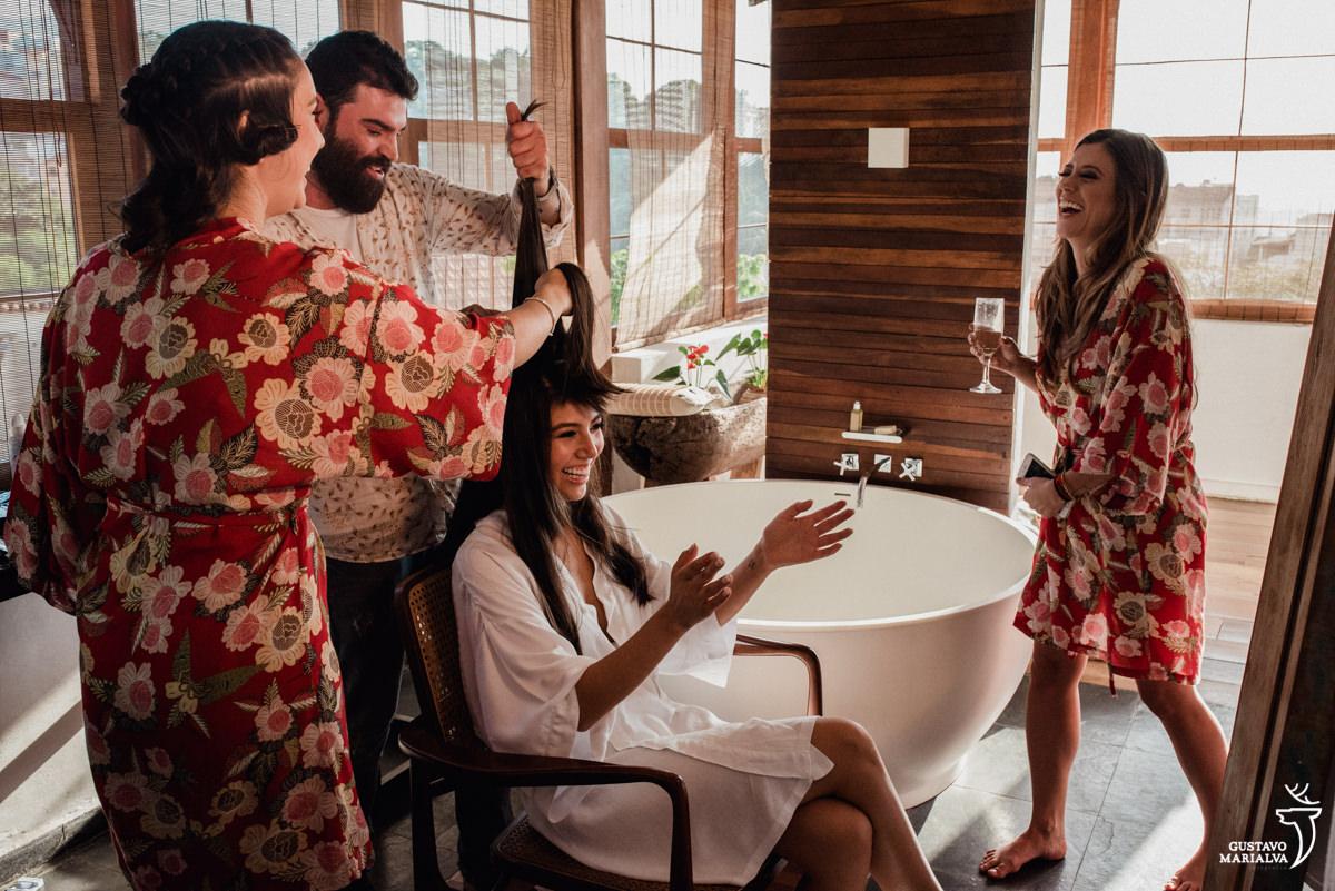 irmã da noiva segura o cabelo da noiva que sorri enquanto é observada pela madrinha sorrindo no making of do casamento no hotel santa teresa