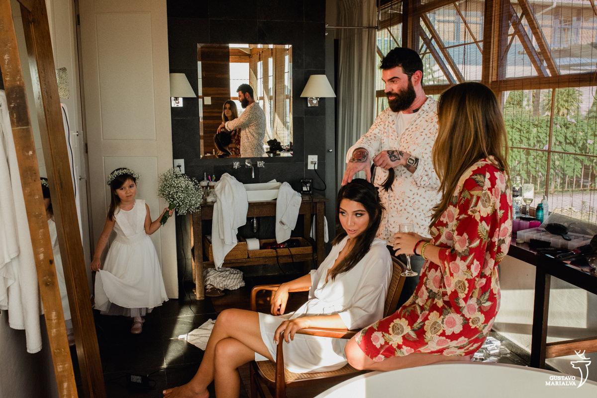 daminha observa a noiva se arrumar segurando o buque enquanto noiva arruma o cabelo durante o making of do casamento no hotel santa teresa
