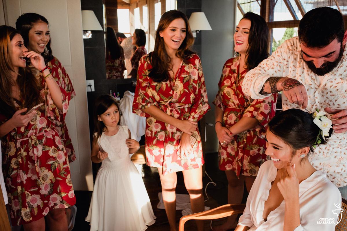 madrinhas e daminha sorriem observando a noiva arrumar o cabelo durante o making of do casamento no hotel santa teresa