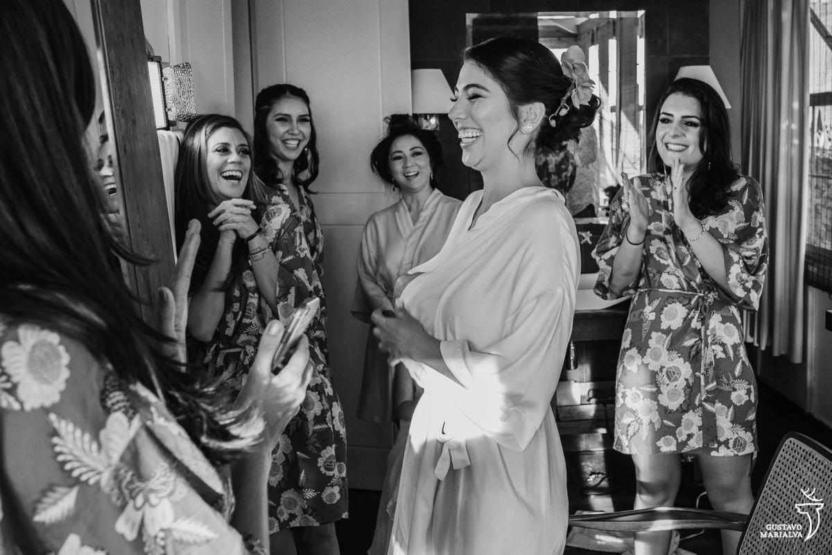 madrinhas emocionadas observam a noiva pronta, que sorri e é aplaudida pela mãe durante o making of do casamento no hotel santa teresa