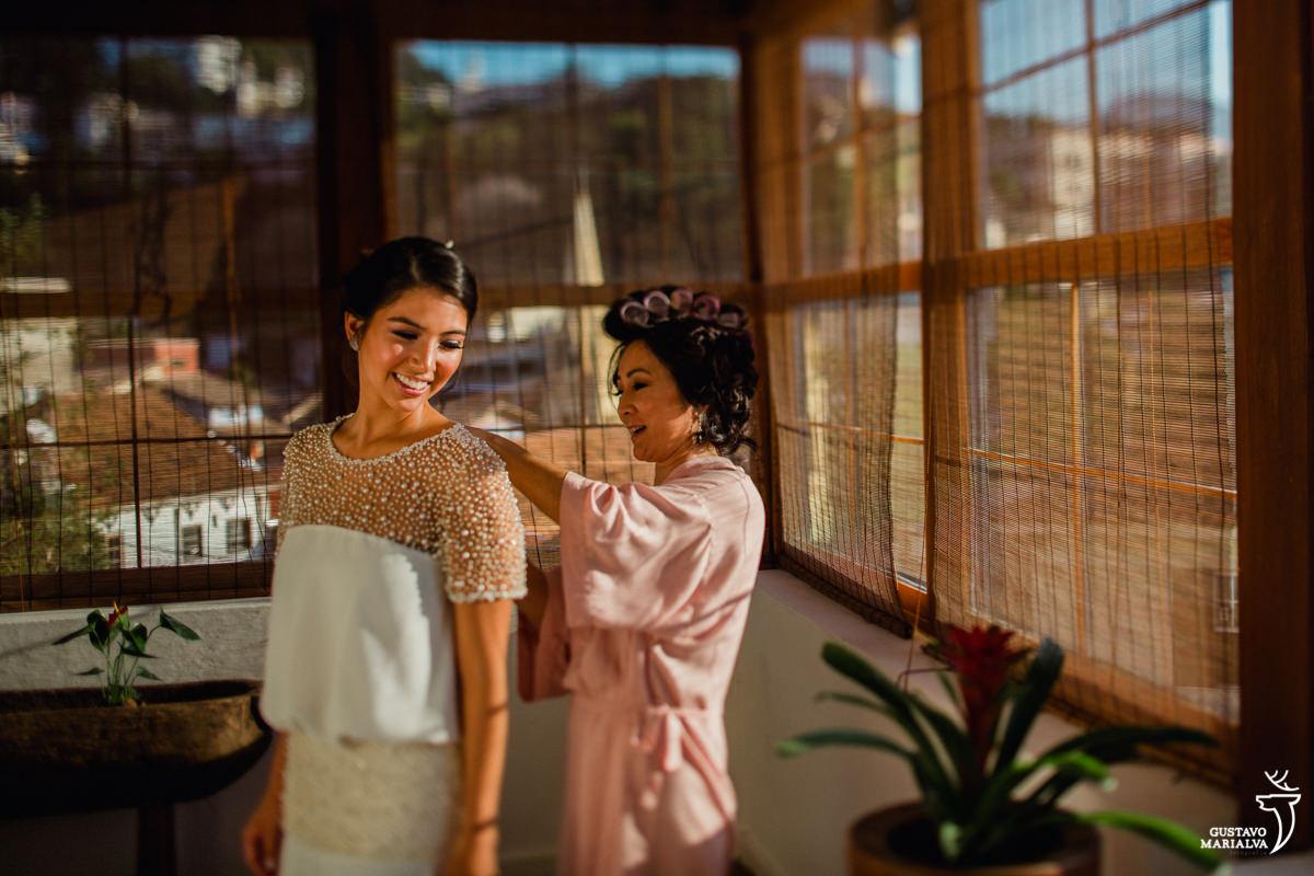 mãe da noiva fecha o vestido de casamento durante o making of do casamento no hotel santa teresa