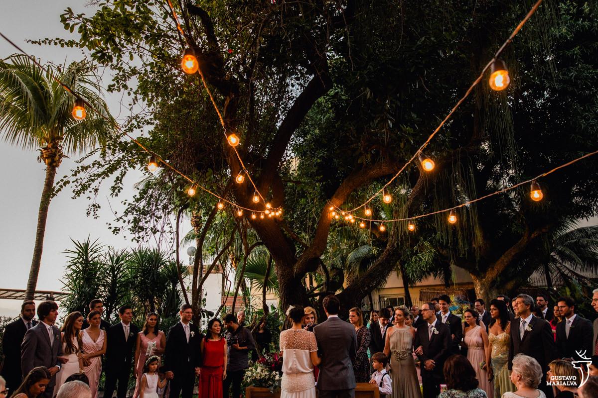 gambiarras colocadas em cima das árvores do hotel santa teresa e convidados observando a cerimônia de casamento