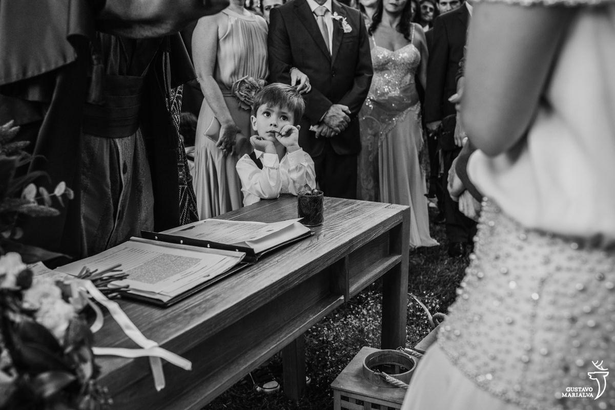 pajem observa a cerimônia de casamento com o dedo na boca