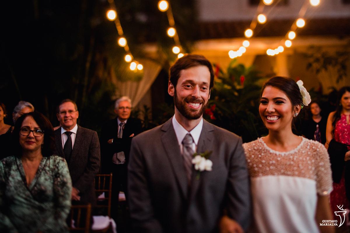 noivos sorriem emocionados durante a cerimônia de casamento