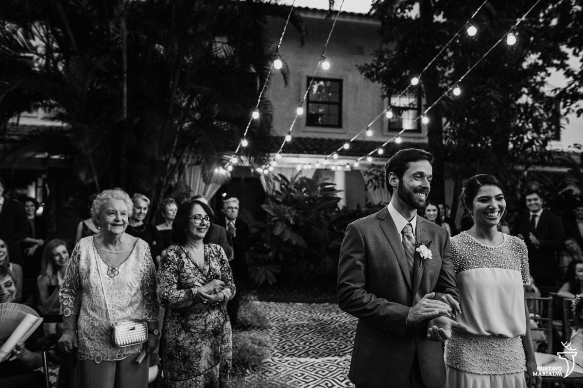 avó do noivo observa a cerimônia de casamento enquanto os noivos sorriem
