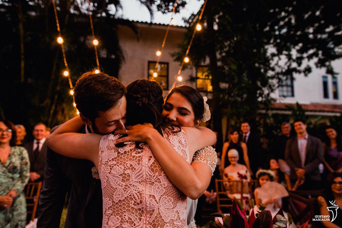 noivos abraçam a irmã da noiva emocionados