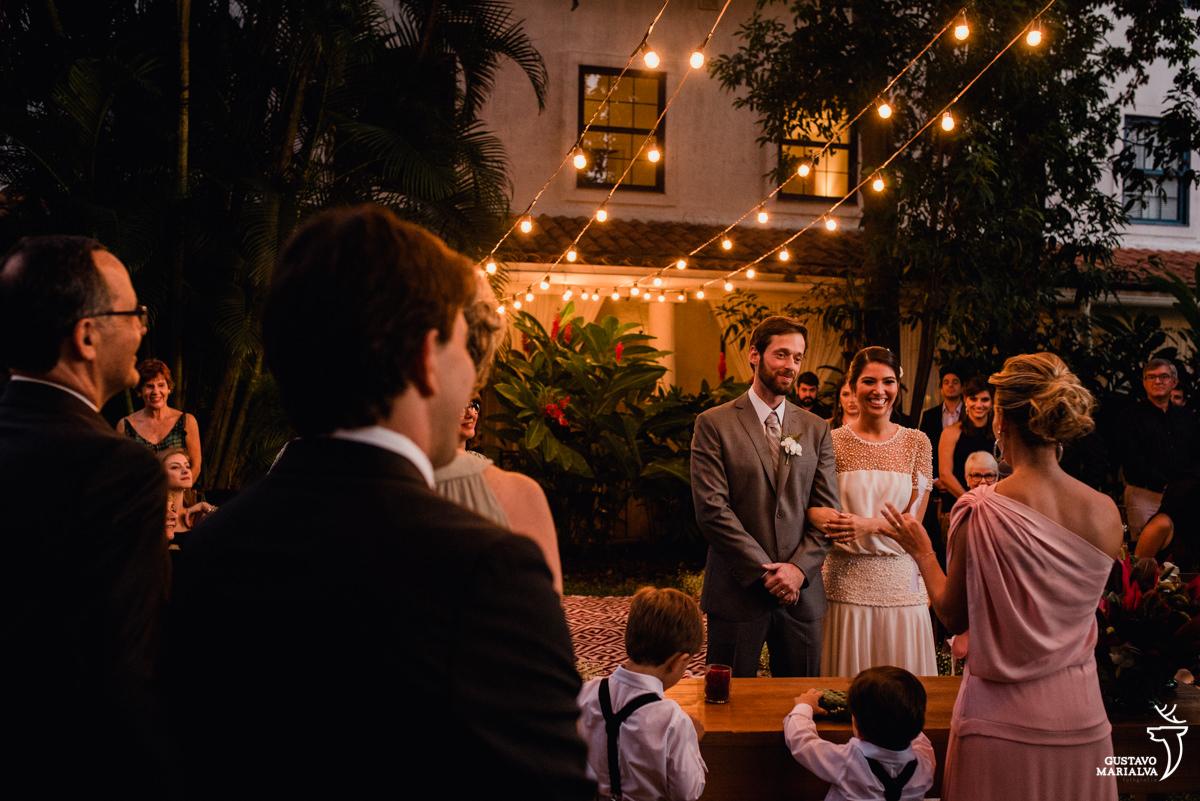 pajens brincam e observam a cerimônia de casamento enquanto os noivos sorriem