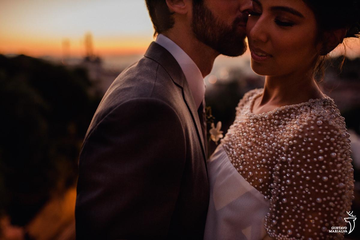 noivo beija a noiva com o por do sol de fundo em santa teresa