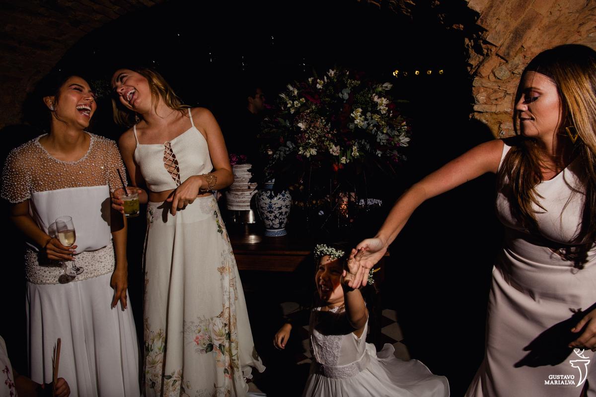 noiva e convidada dançam sorrindo enquanto madrinha roda a daminha