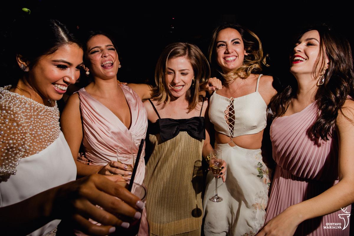 noiva e amigas pulam abraçadas e sorridentes