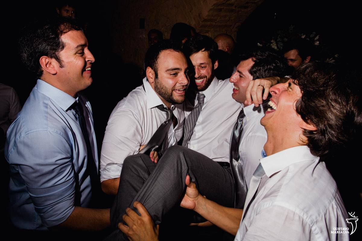 padrinhos carregam o noivo no colo que sorri