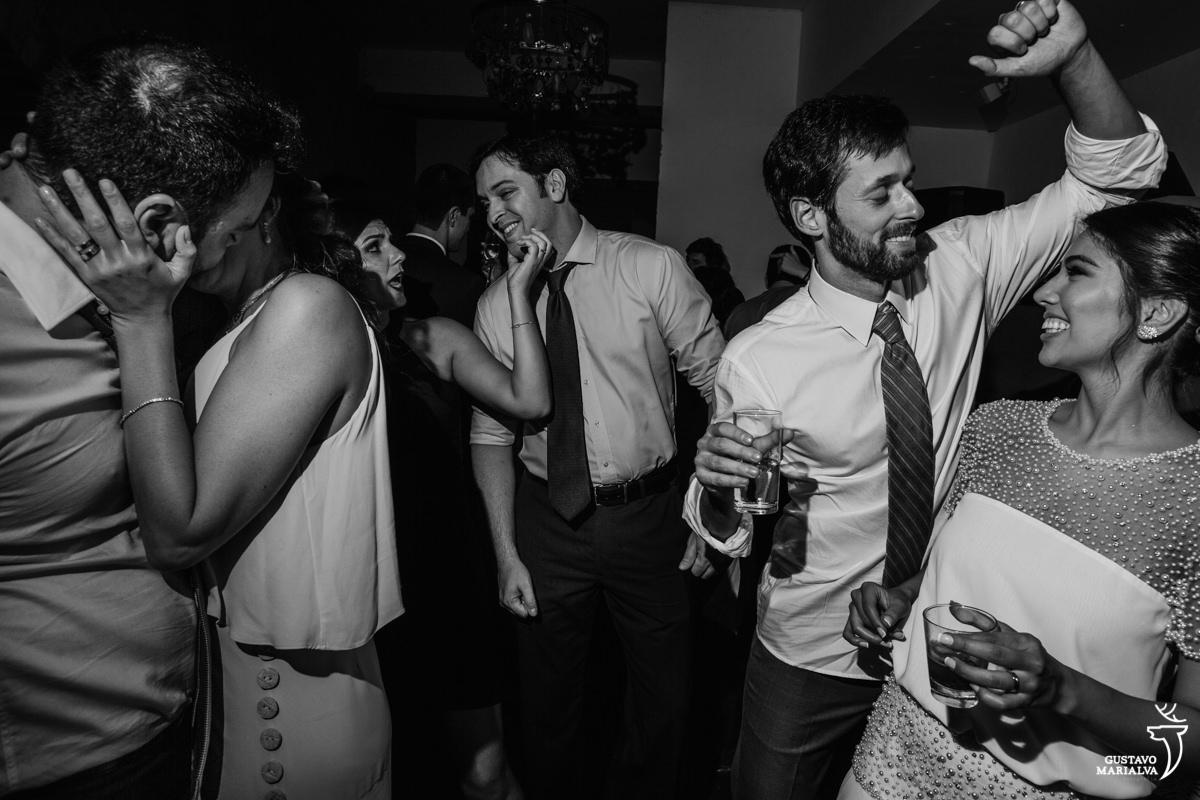 noivos dançam enquanto convidados se beijam