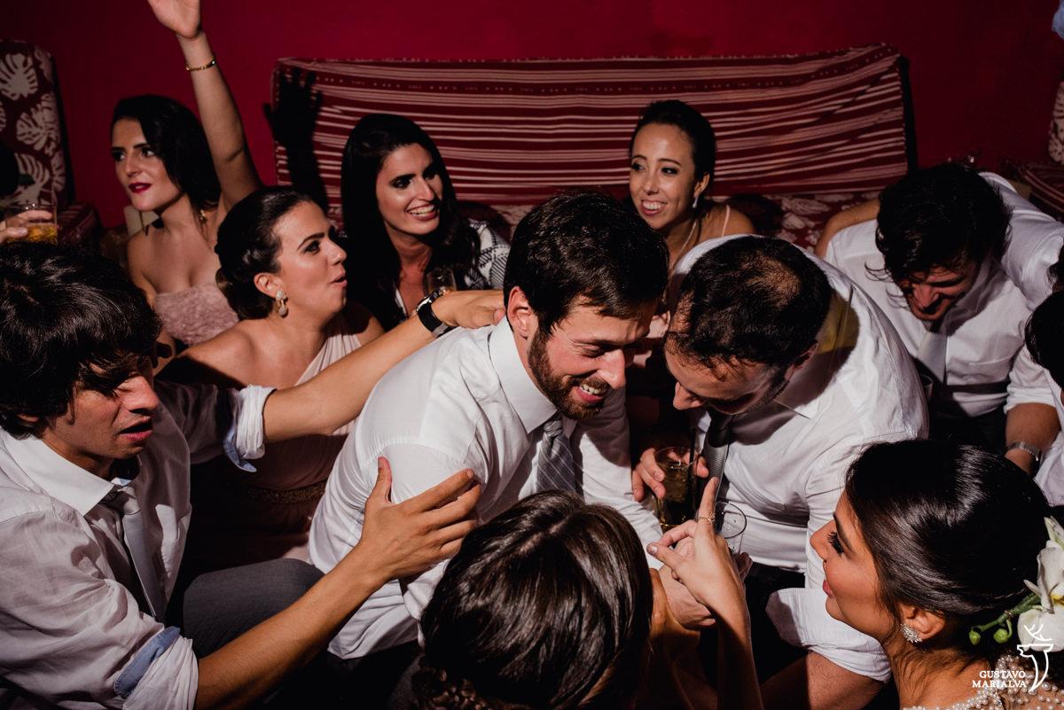 noivos e amigos se agacham até o chão sorrindo