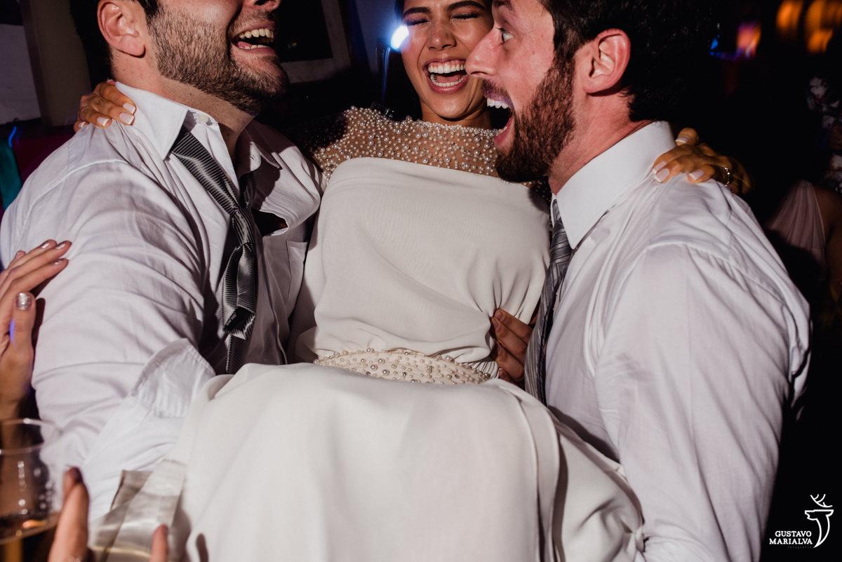 noivo e padrinho carregam a noiva no colo sorridente