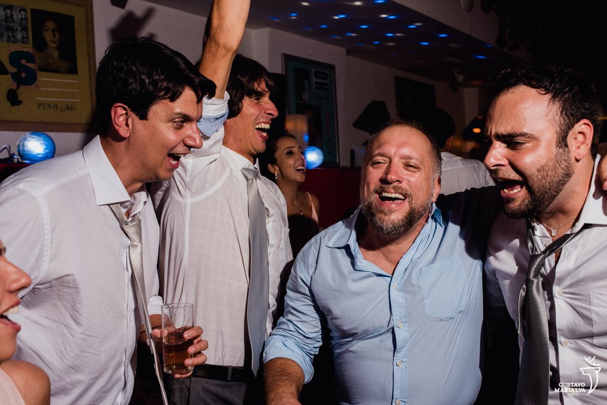amigos dançam com copo na mão sorrindo no hotel santa teresa