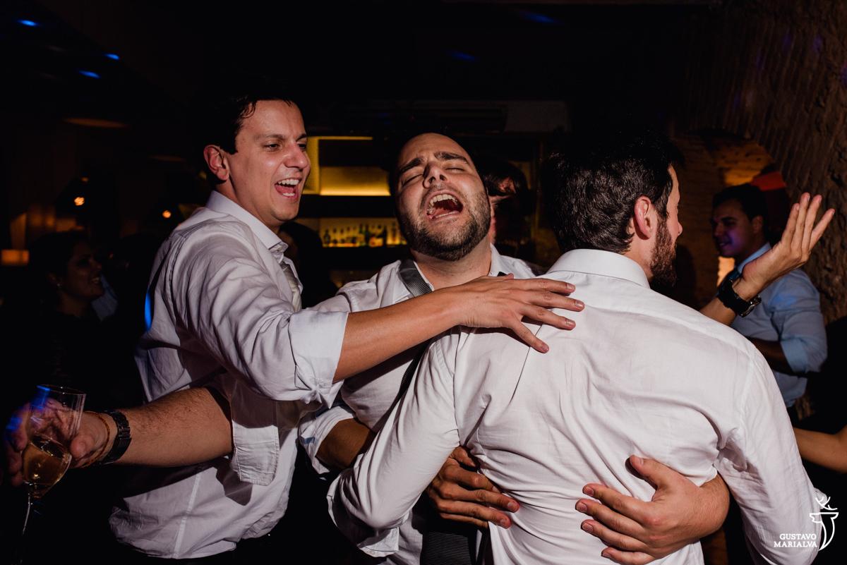 amigo cantam empolgados durante a festa de casamento