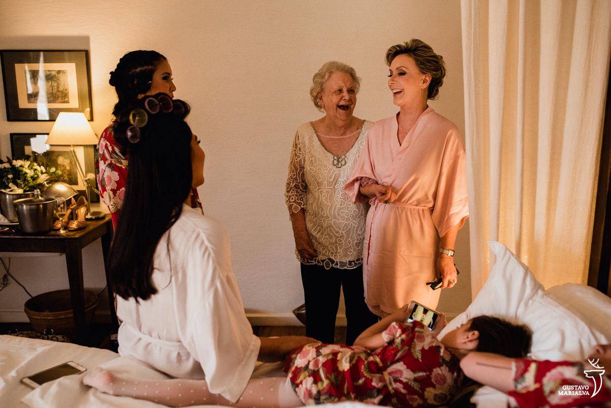 avó do noivo e mãe sorriem sendo observadas pela noiva enquanto daminha joga no celular deitada na cama