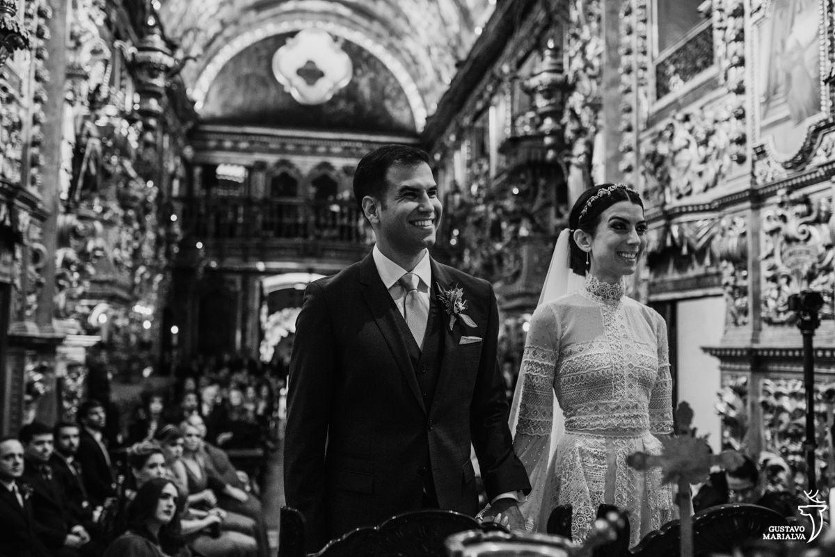 noivo sorriem de mãos dadas durante a cerimônia de casamento