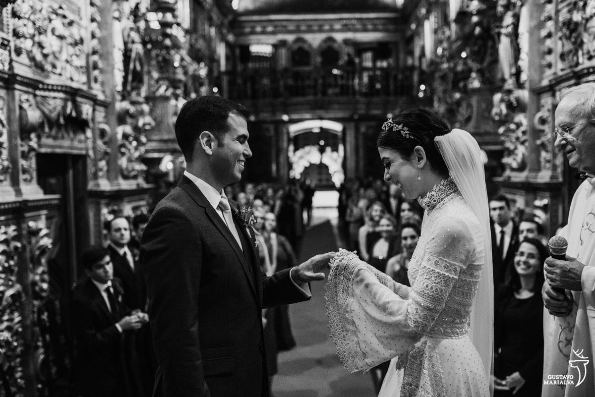 noiva coloca aliança no noivo e sorri durante a cerimônia de casamento