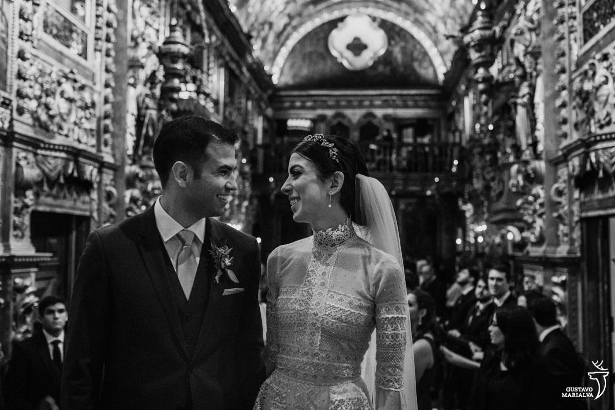 noivos se olham e sorriem durante a cerimônia de casamento