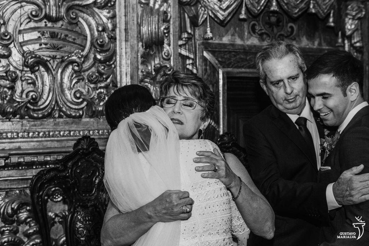 noiva abraça a mãe emocionada e noivo abraça o sogro