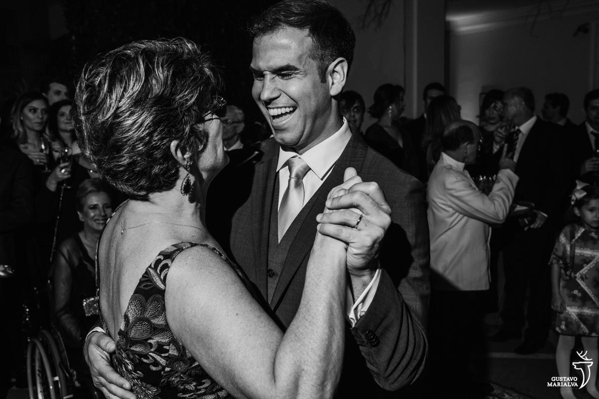noivo sorridente dança com a mãe da noiva