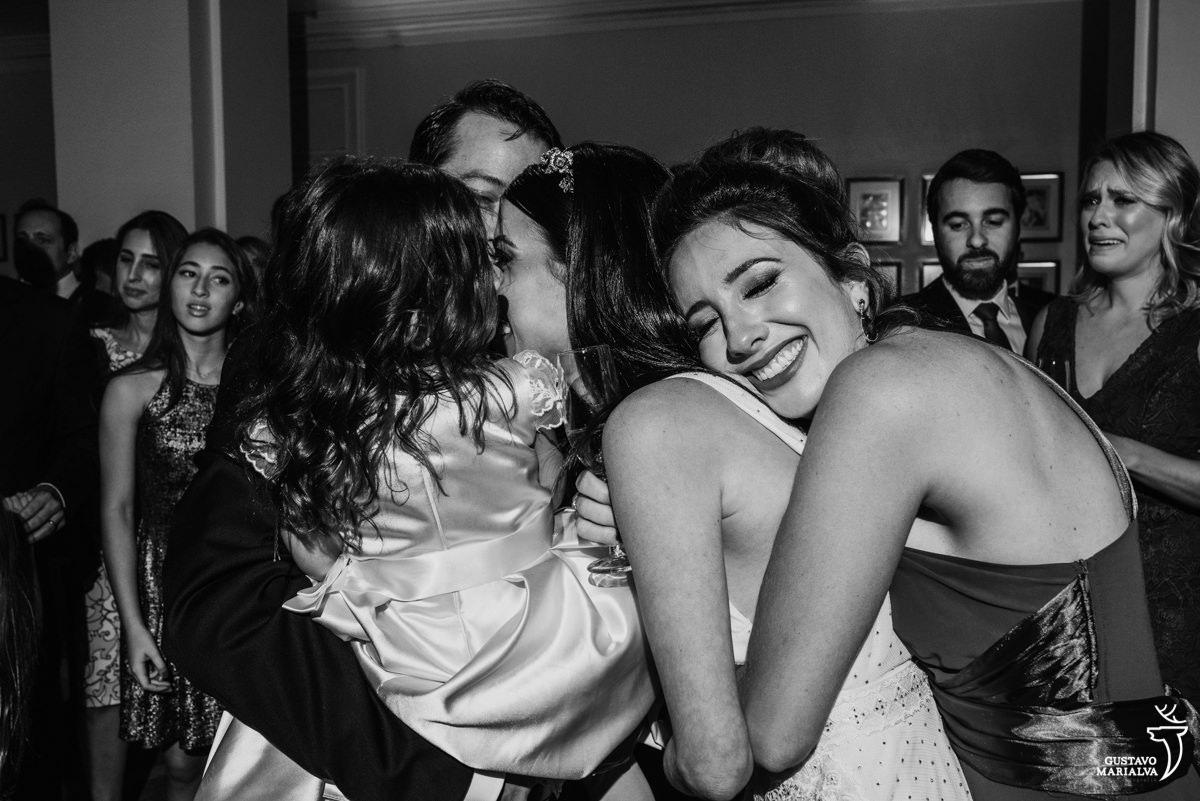 convidada abraça a noiva e madrinha chora ao fundo