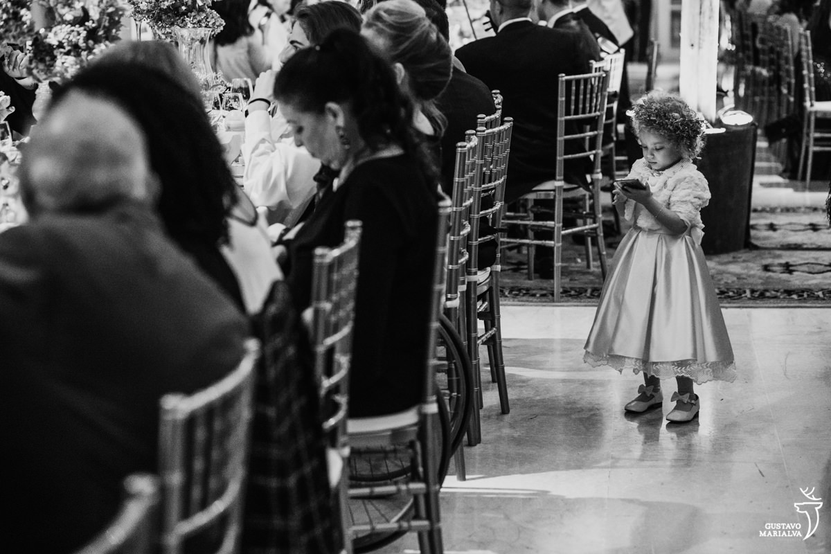 daminha brinca com celular durante a festa de casamento