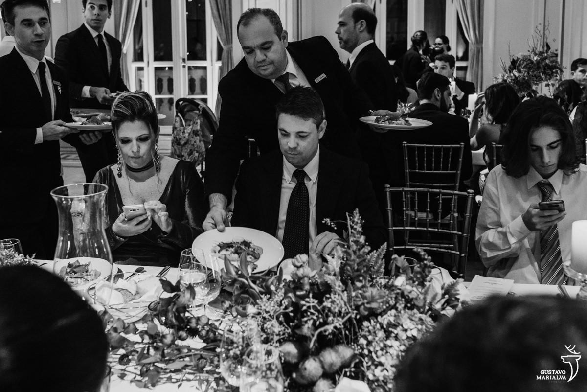 garçom serve prato para convidado enquanto mulher e menino olham o celular