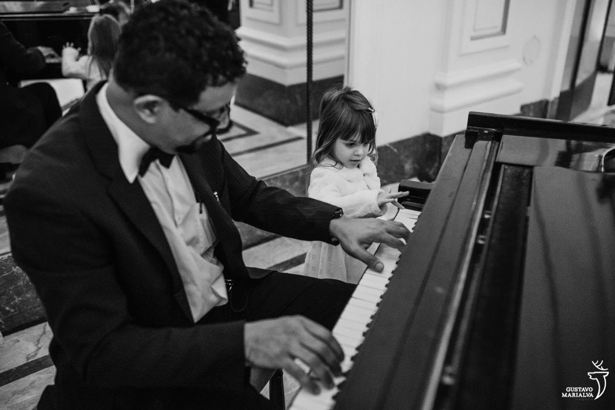 daminha observa músico tocar o piano