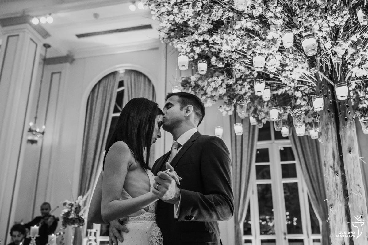 noivos dançam e noivo beija a testa da noiva com árvore repleta de velas ao fundo