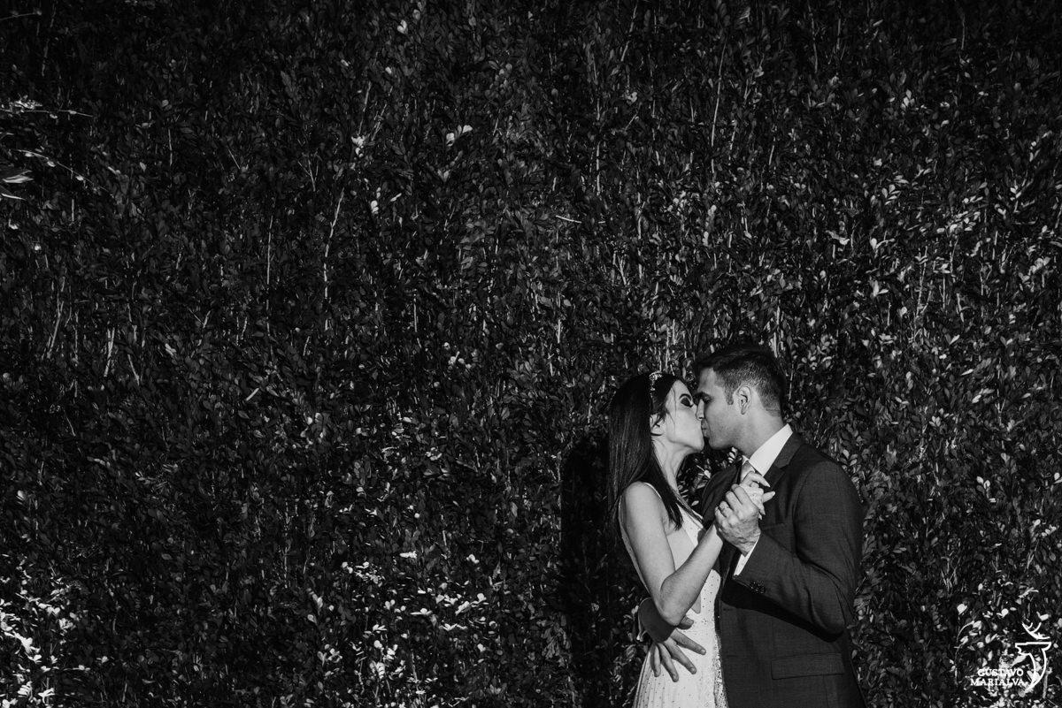 noivos dançam e se beijam em frente a parede de grama