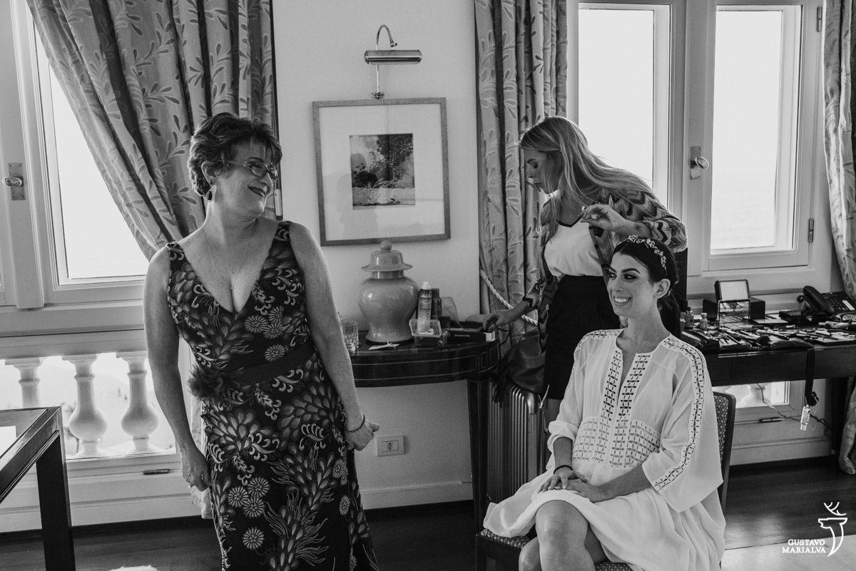 mãe da noiva mostrando o vestido enquanto a noiva sorri durante o  making of no hotel copacabana palace