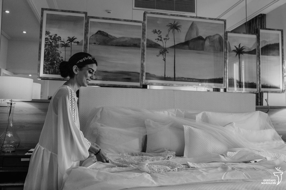 noiva arrumando o vestido na cama do hotel copacabana palace