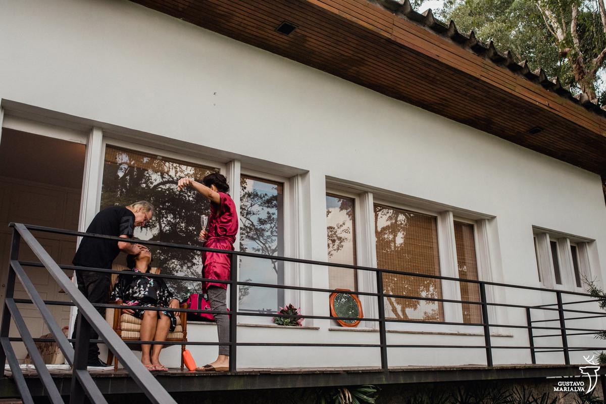 noiva sendo maquiada na varanda do Recanto do Barão enquanto é observada por amiga