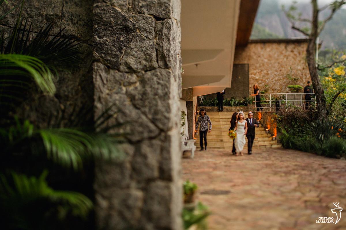 noiva a caminho da cerimônia segurando o buquê acompanhada do pai e da cerimonialista