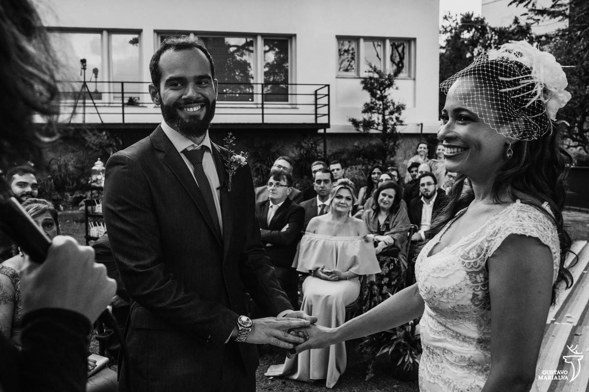 noivos sorrindo segurando as mãos sendo observados pelos convidados