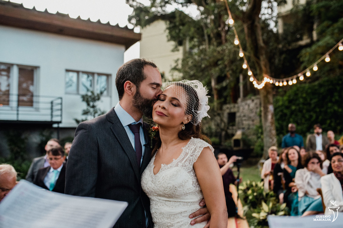 noivo beijando a noiva de olhos fechados