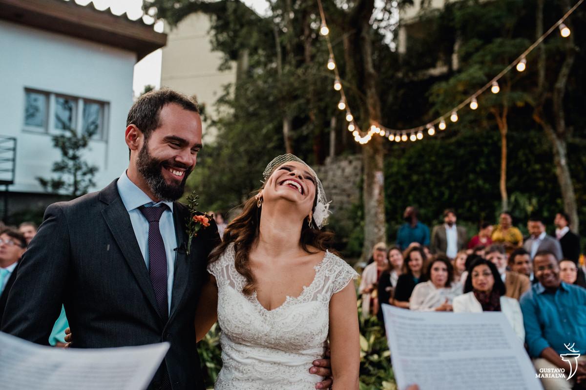 noivos sorrindo com discursos dos amigos durante a cerimônia de casamento