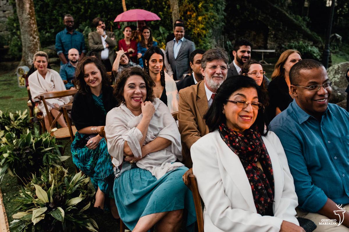 convidados sorrindo emocionados durante a cerimônia de casamento