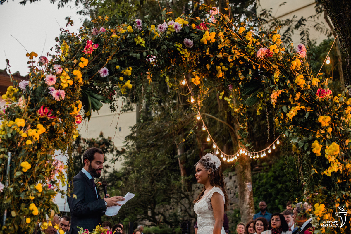 noivo lendo os votos para a noiva com arco de flores e gambiarras penduradas na árvores