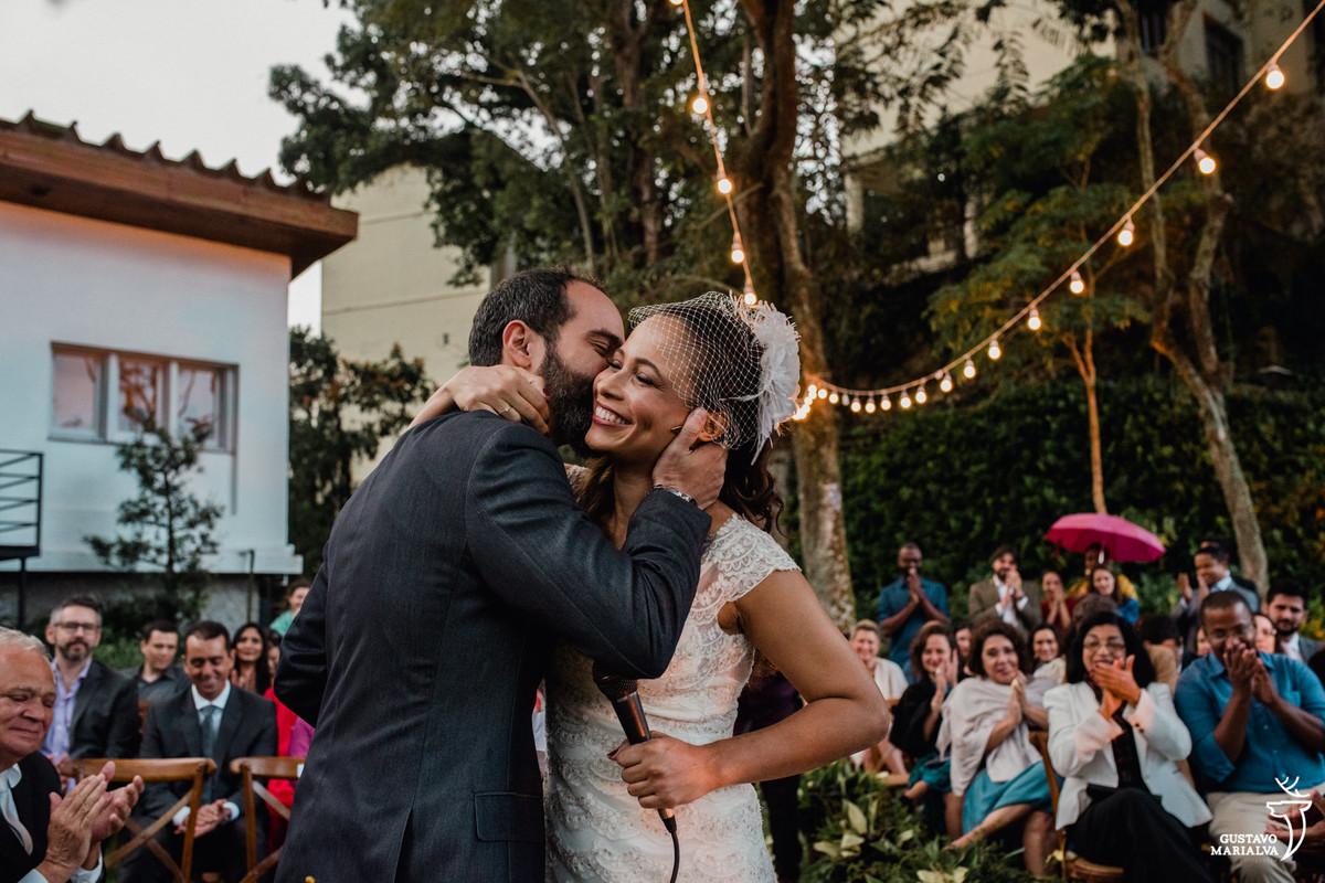 noivo beijando a noiva que segura o microfone