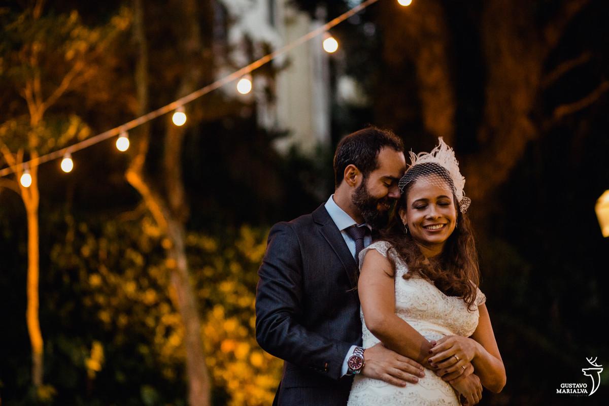noivo abraçando a noiva por trás colocando a testa na testa dela
